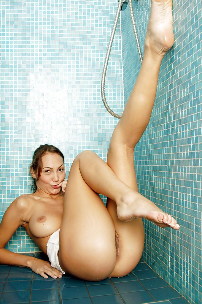 Грудастая молодая девица принимает душ в одежде и мастурбирует киску - секс порно фото