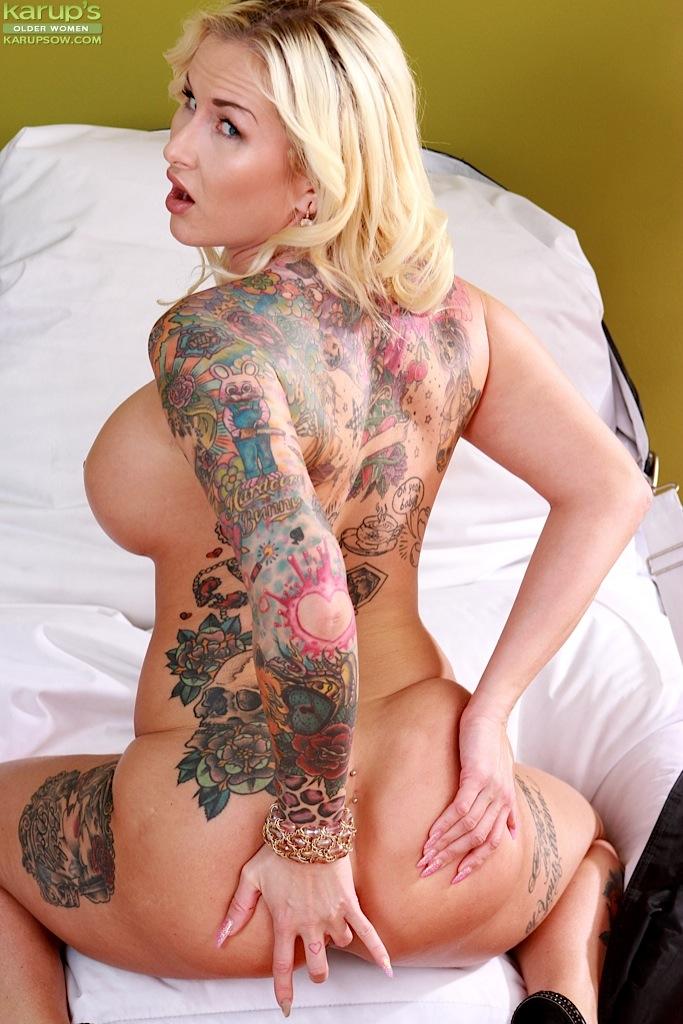 Зрелая татуированная блондинка оголяет большие сиськи и задницу перед мастурбацией - секс порно фото