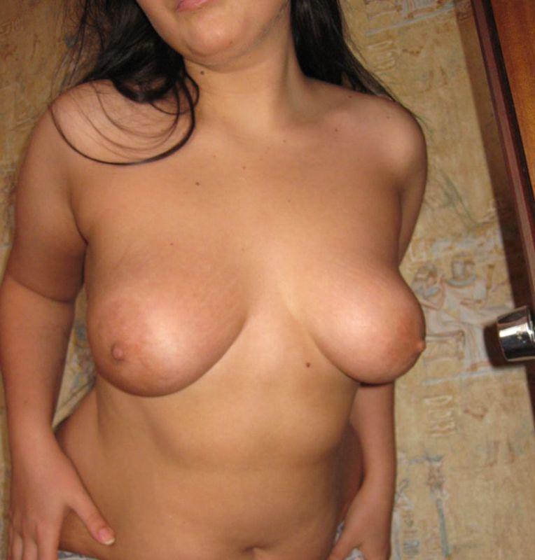 Молодая брюнетка обнажает сиськи и выбритую вульву - секс порно фото