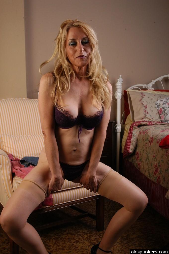 Зрелая блондинка Robin в бежевых чулках раздевается в спальне - секс порно фото