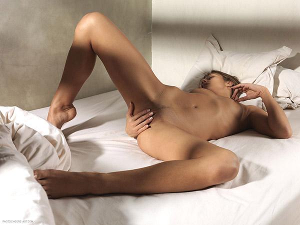 Голая красотка мастурбирует на кровати - секс порно фото